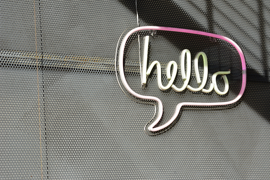 Neon sign in the shape of a speech bubble that says 'hello' hanging on a metal wall